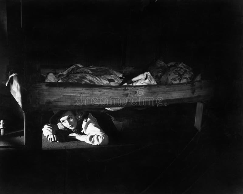 Junge Frau, die unter dem Bett sich versteckt (alle dargestellten Personen sind nicht längeres lebendes und kein Zustand existier lizenzfreies stockfoto