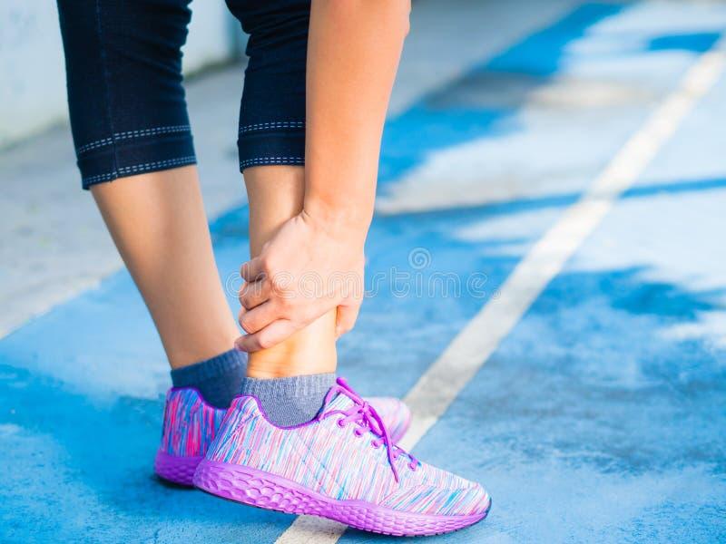Junge Frau, die unter einer Knöchelverletzung beim Trainieren und Laufen leidet stockfotos