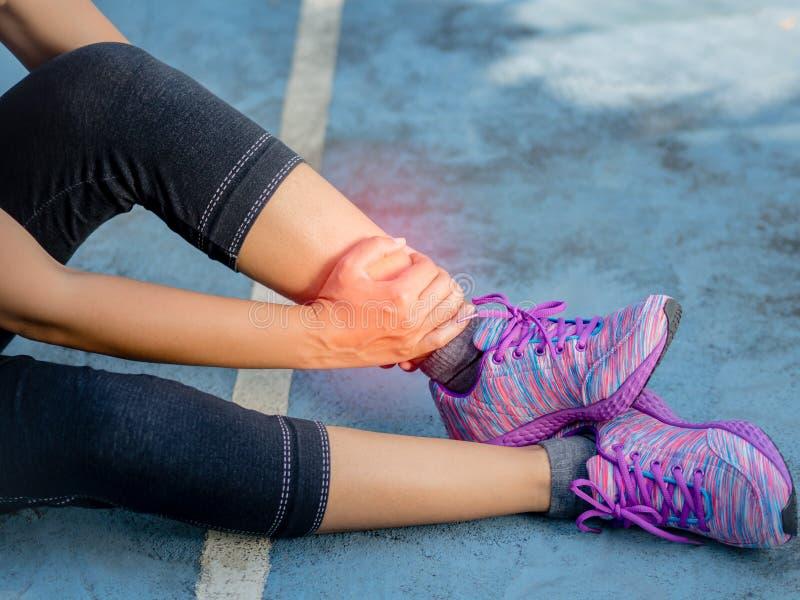 Junge Frau, die unter einer Knöchelverletzung beim Trainieren und Laufen leidet stockfotografie