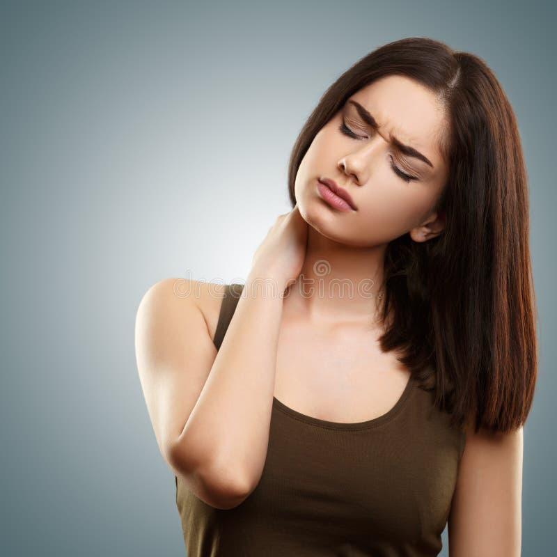Junge Frau, die unter Nackenschmerzen leidet stockbild