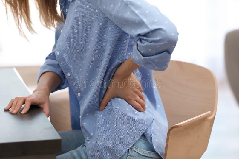Junge Frau, die unter Rückenschmerzen im Büro leidet stockfoto