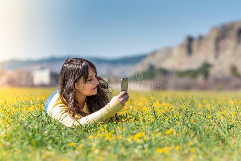 Junge Frau, die unter Verwendung des Handys niederlegt lizenzfreies stockfoto