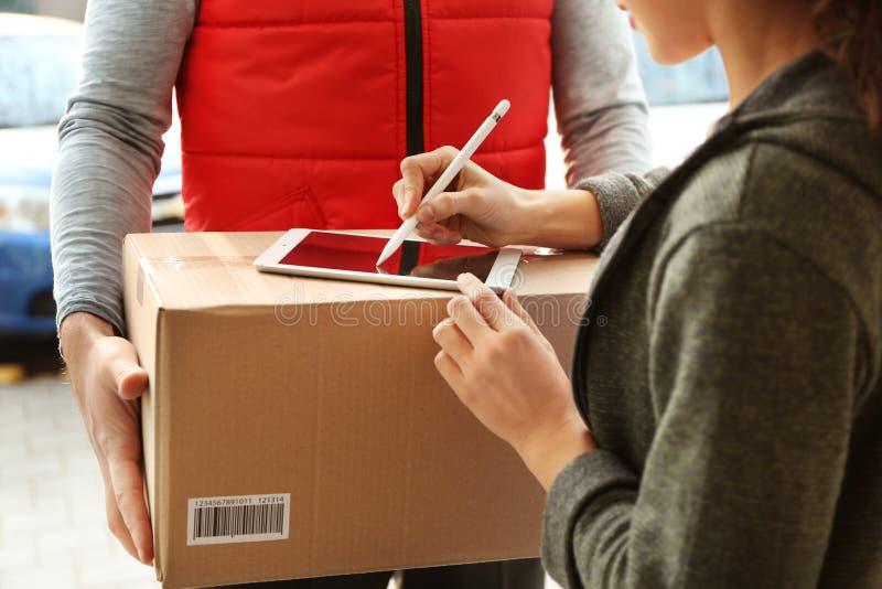Junge Frau, die Unterzeichnung hinzufügt, nachdem Paket empfangen worden ist lizenzfreies stockfoto