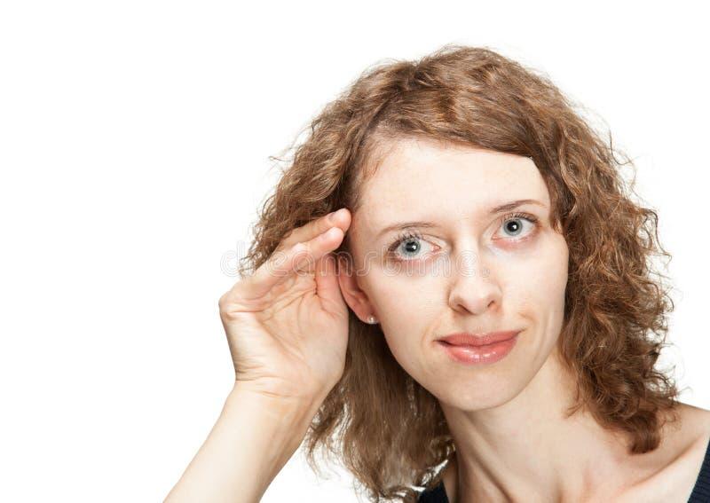 Junge Frau, die versucht, etwas zu hören lizenzfreie stockbilder