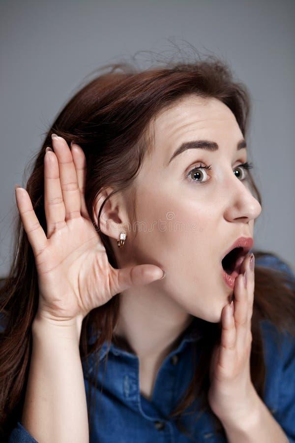 Junge Frau, die versucht, zu hören etwas lizenzfreies stockbild