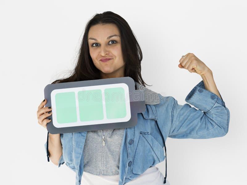 Junge Frau, die volle Batterie auf ihrer Hand hält lizenzfreies stockbild