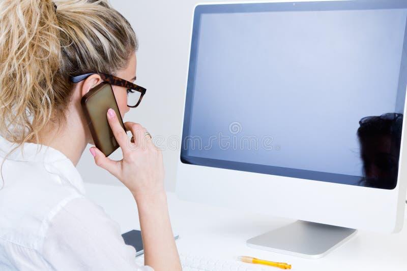 Junge Frau, die vom Haus auf dem Computer arbeitet und auf spricht stockfoto