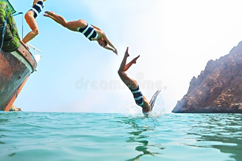 Junge Frau, die von einem Segelboot springt stockfotos