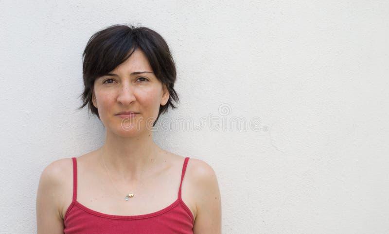 Junge Frau, die vor einer Wand steht lizenzfreies stockfoto