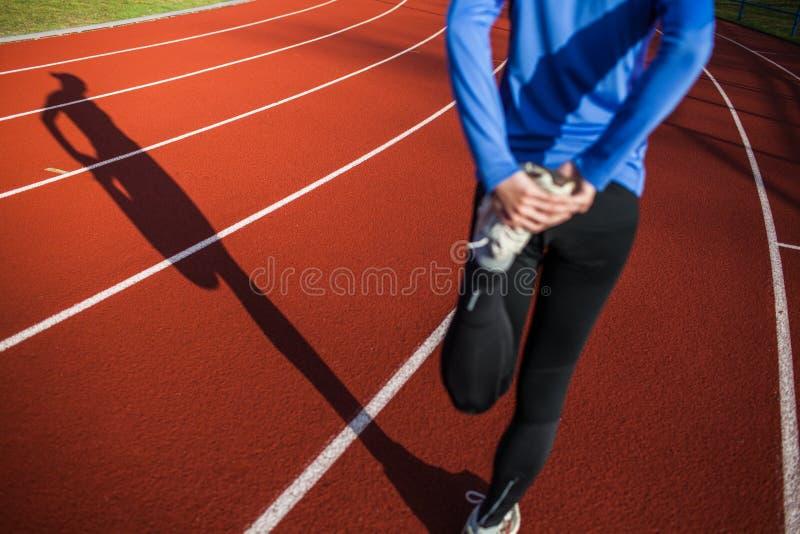 Junge Frau, die vor ihrem Lack-Läufer ausdehnt lizenzfreies stockbild