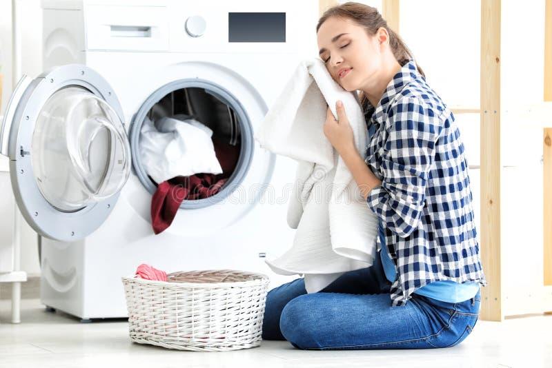 Junge Frau, die Wäscherei tut stockfoto