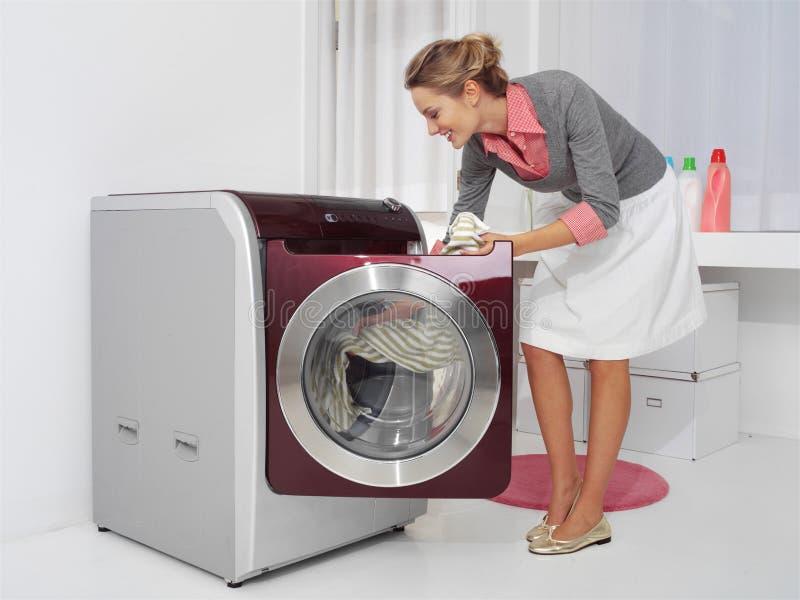Junge Frau, die Wäscherei tut stockbilder