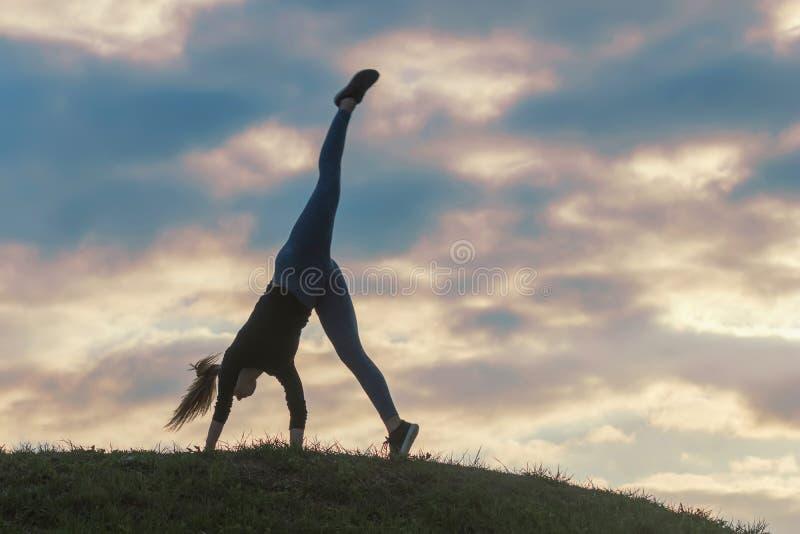 Junge Frau, die Wagenrad auf dem schönen Sonnenaufgang Gras Morgengymnastik tut stockfotografie