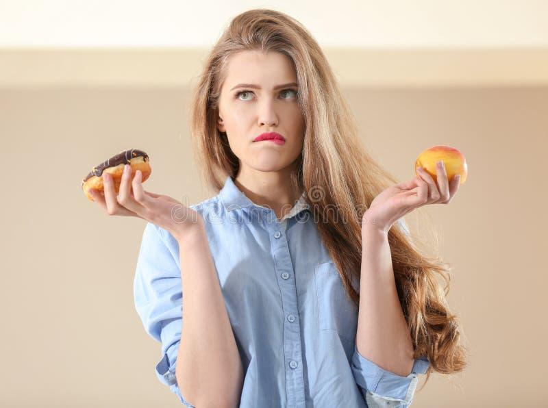 Junge Frau, die Wahl zwischen Apfel trifft stockfotografie