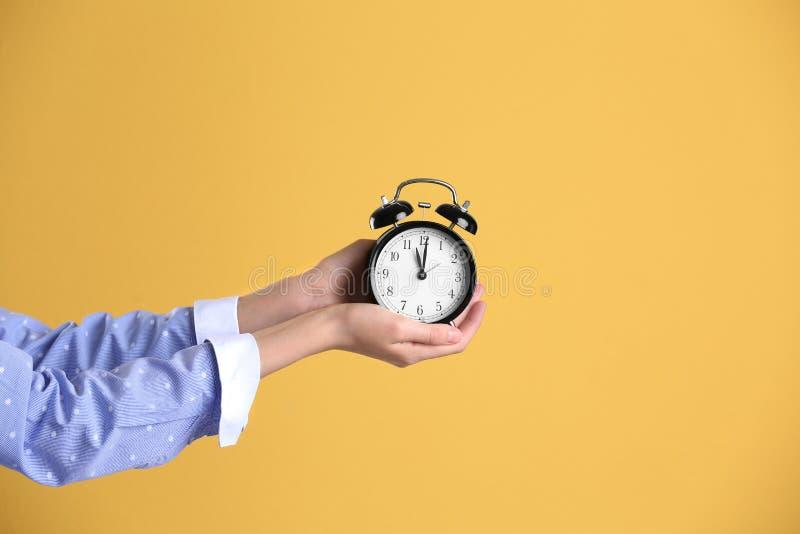 Junge Frau, die Wecker auf gelbem Hintergrund hält Setzen Sie Zeit Konzeptes fest Wenden Sie getrennt auf weißem Hintergrund ein stockbild