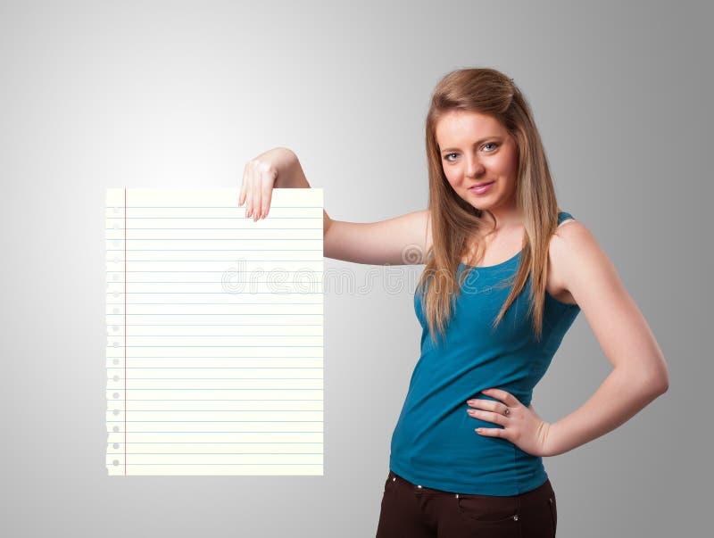 Junge Frau, die Weißbuchkopienraum mit diagonalen Linien hält stockfoto