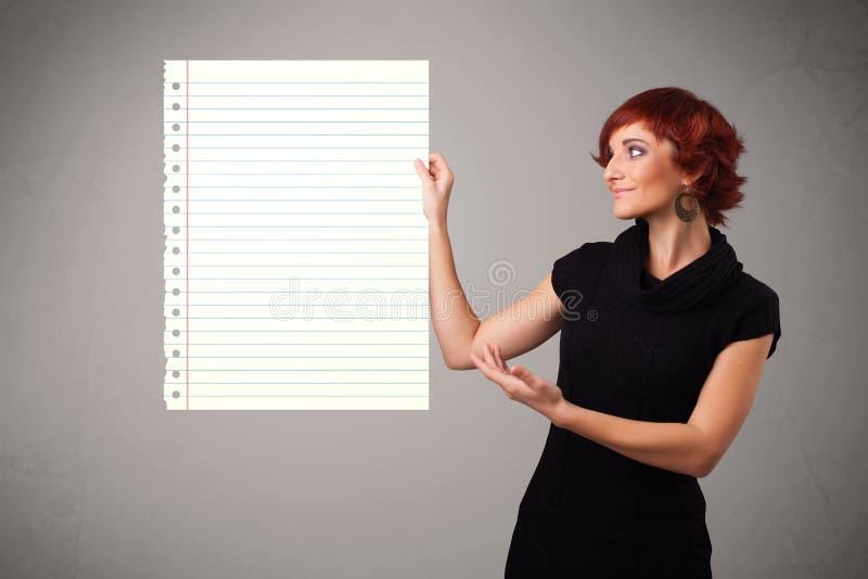 Junge Frau, die Weißbuchkopienraum mit diagonalen Linien hält lizenzfreie stockbilder