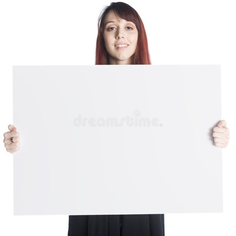 Junge Frau, die weißen Vorstand anhält stockbild