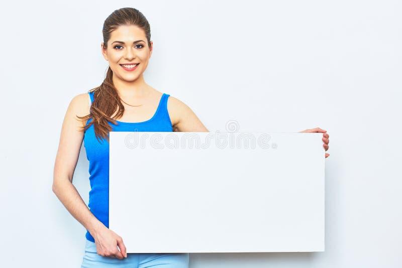 Junge Frau, die weißes leeres Schild hält lizenzfreie stockfotos