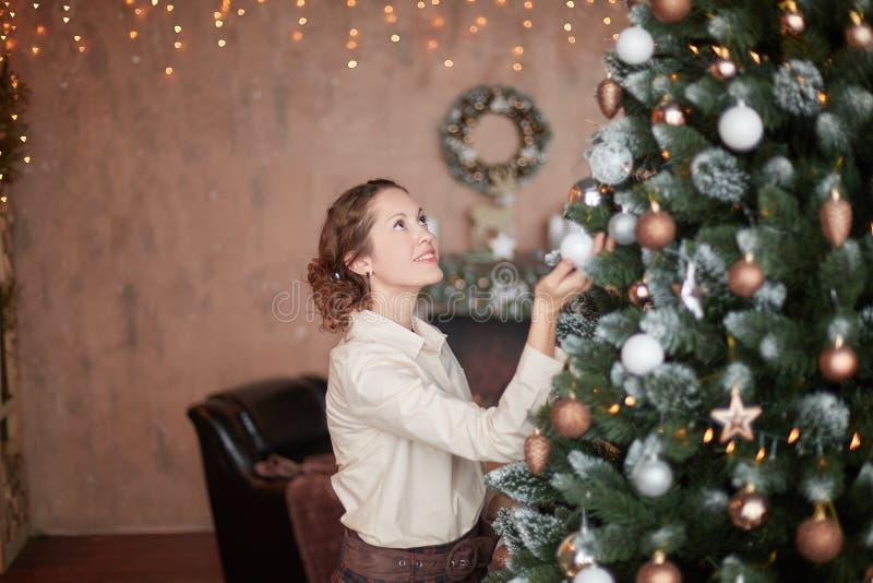 Junge Frau, die Weihnachtsbaum in ihrem Wohnzimmer verziert lizenzfreies stockfoto