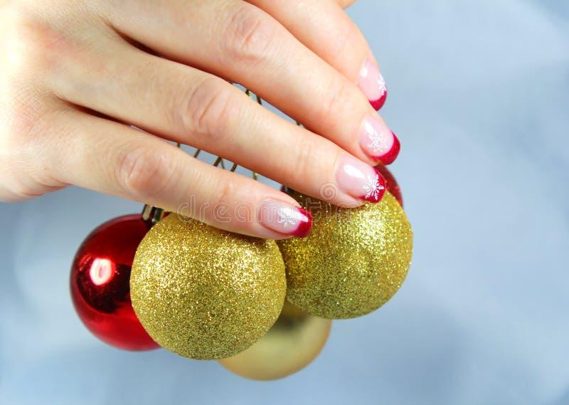 Junge Frau, die Weihnachtsverzierungen in ihren Händen hält stockfoto
