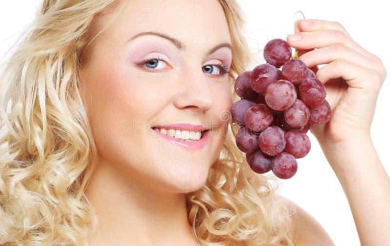 Junge Frau, die Weintraube hält stockbild