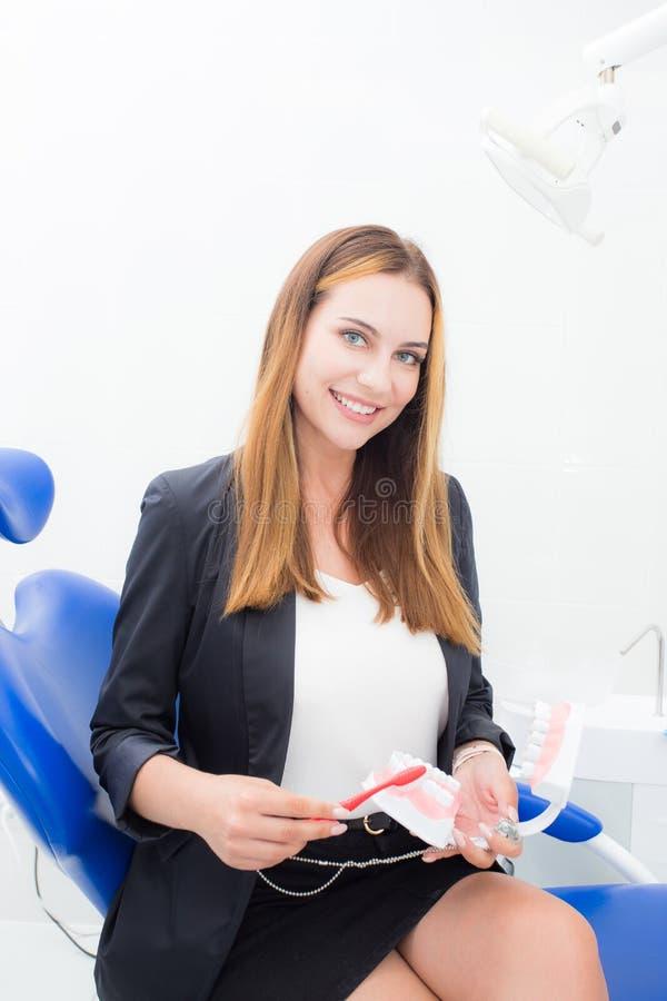Junge Frau, die wie man Ihre Zähne zeigt, säubert stockbilder