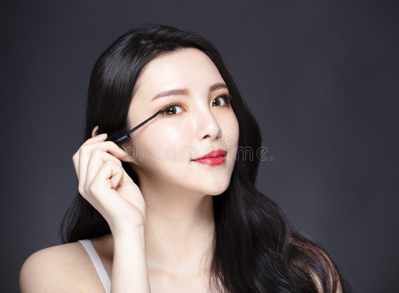 Junge Frau, die Wimperntusche des blauen Auges auf ihre Wimpern zutrifft lizenzfreies stockfoto