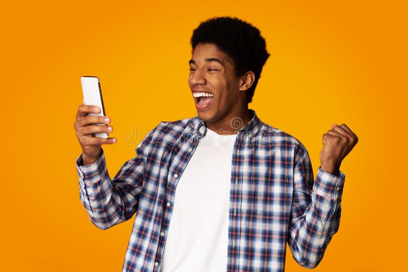 Junge Frau, die yeah kreischt! in der Freude Afrikaner Guy Using Smartphone im Studio stockbild