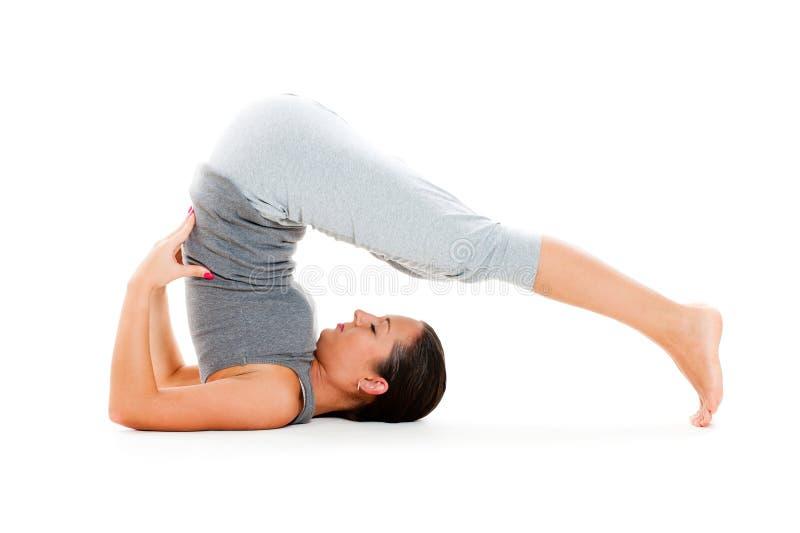 Junge Frau, die Yogaübung tut stockfotografie
