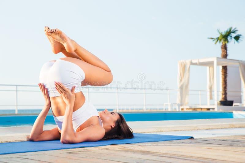 Junge Frau, die Yogaübungen macht lizenzfreie stockfotos