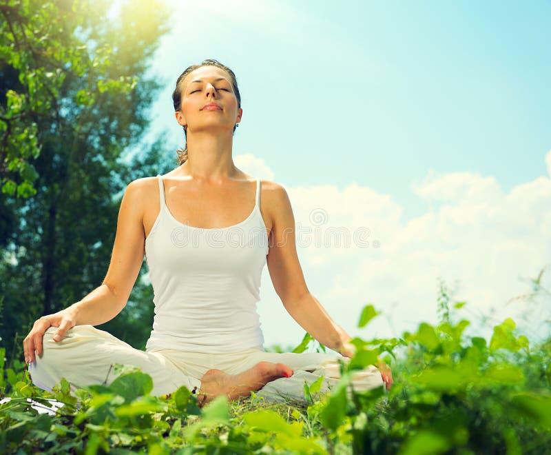 Junge Frau, die Yogaübungen tut stockbild