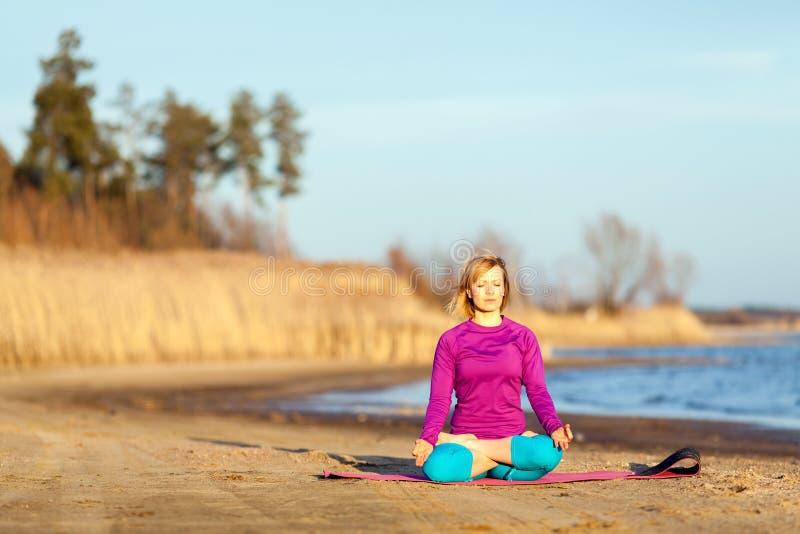 Junge Frau, die Yoga auf Sonnenuntergang ausübt lizenzfreie stockfotos