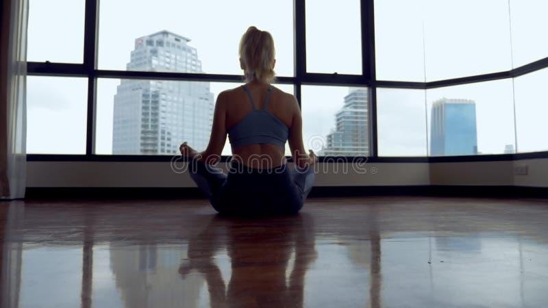 Junge Frau, die Yoga in einem Raum nahe einem großen Fenster übersieht die Wolkenkratzer tut stockbild
