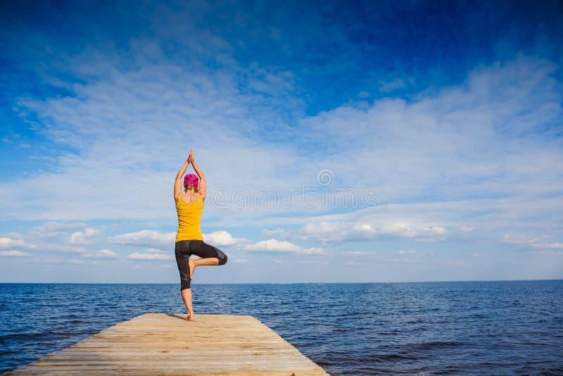 Junge Frau, die Yoga-Haltung tut stockfoto