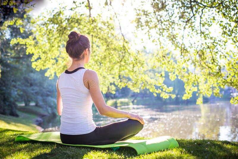 Junge Frau, die Yoga im Morgenpark nahe See tut lizenzfreies stockfoto