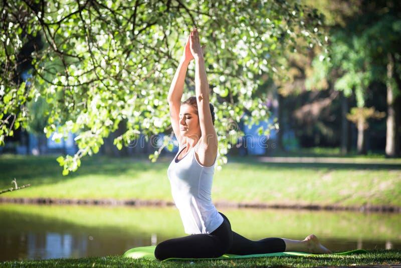 Junge Frau, die Yoga im Morgenpark nahe See tut lizenzfreie stockfotografie