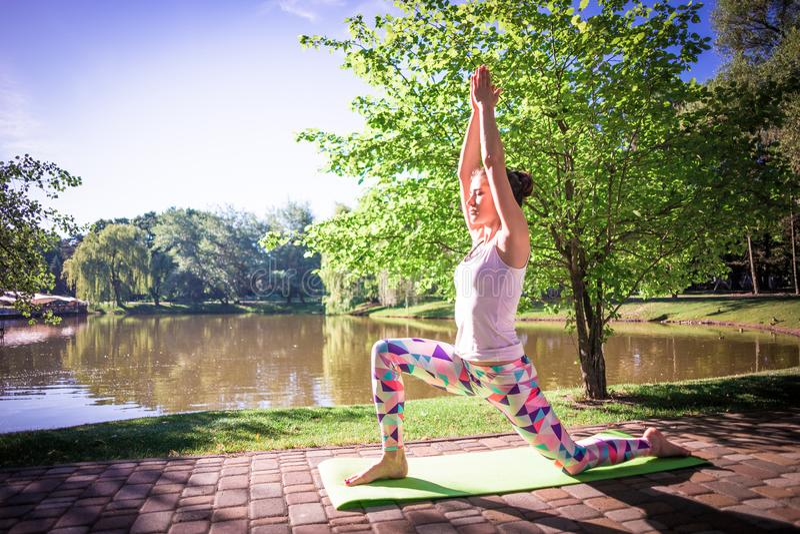 Junge Frau, die Yoga im Morgenpark nahe See tut lizenzfreie stockfotos