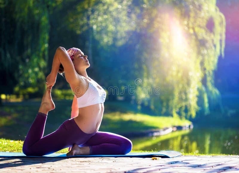 Junge Frau, die Yoga am schönen Morgen nahe See tut lizenzfreie stockbilder