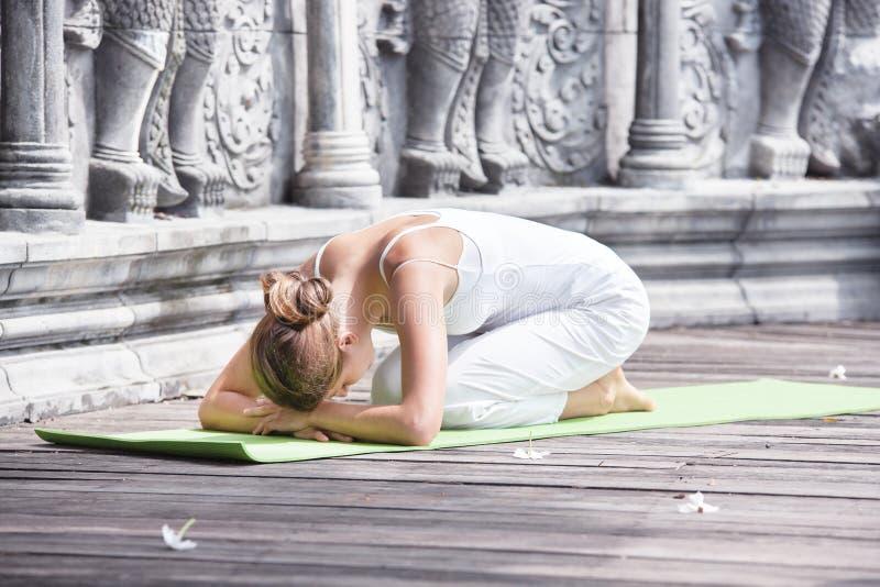Junge Frau, die Yoga in verlassenem Tempel auf hölzerner Plattform tut Üben lizenzfreies stockfoto