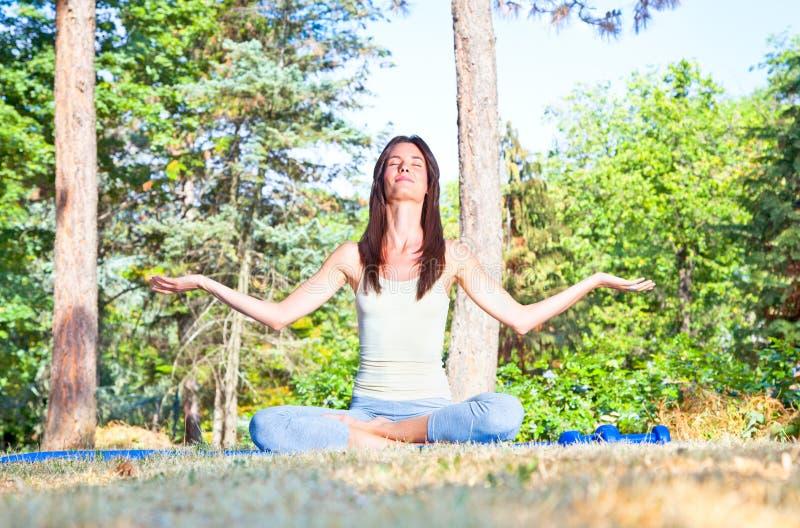 Junge Frau, die Yogameditation im Wald tut stockbild