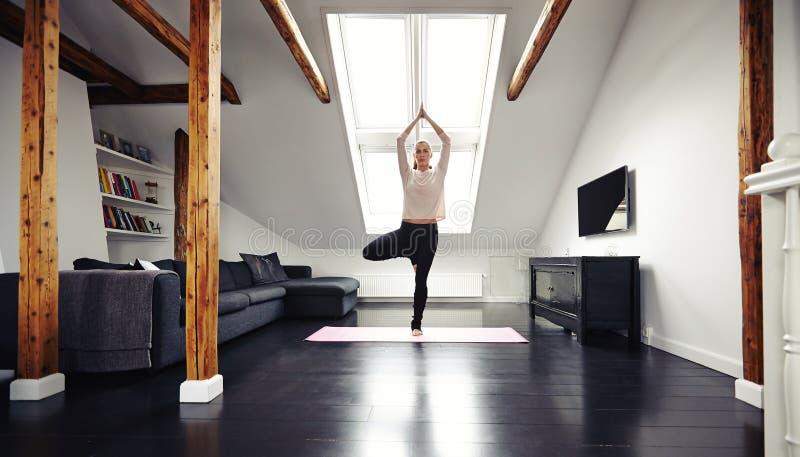 Junge Frau, die in Yogaposition steht stockbilder