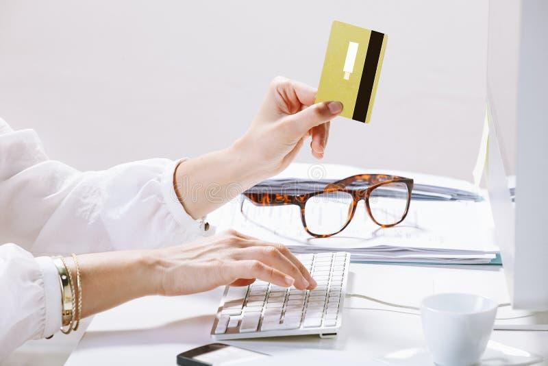 Junge Frau, die Zahlungen on-line beim Schreiben auf den Computer leistet lizenzfreie stockfotos