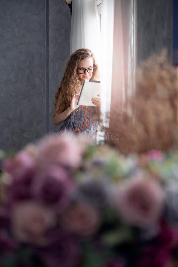 Junge Frau, die zu Hause an digitalem Tablet-Computer arbeitet lizenzfreies stockfoto
