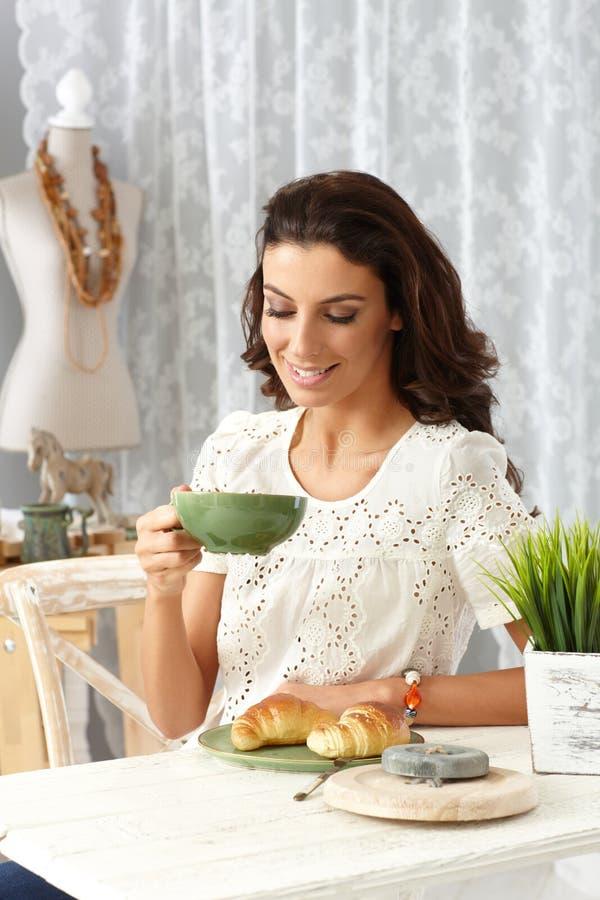 Junge Frau, die zu Hause frühstückt lizenzfreie stockbilder