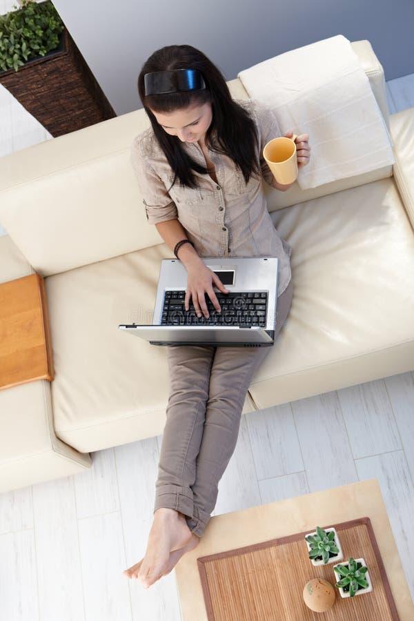 Junge Frau, die zu Hause Laptop verwendet stockfoto
