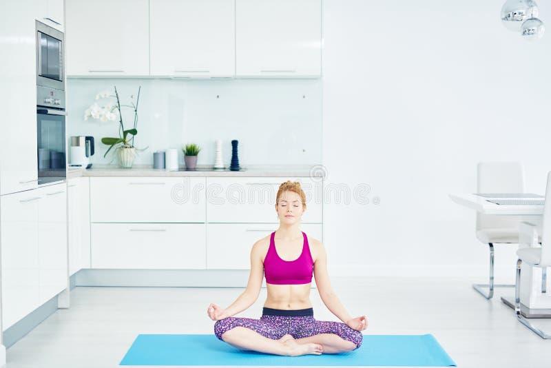 Junge Frau, die zu Hause in Lotus Pose sitzt lizenzfreie stockfotos