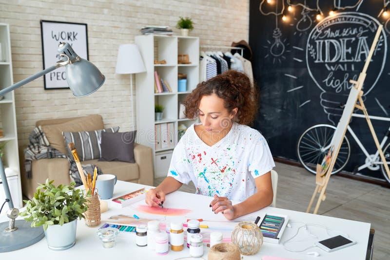 Junge Frau, die zu Hause malt stockbilder