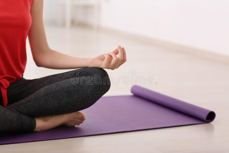 Junge Frau, die zu Hause meditiert stockfoto