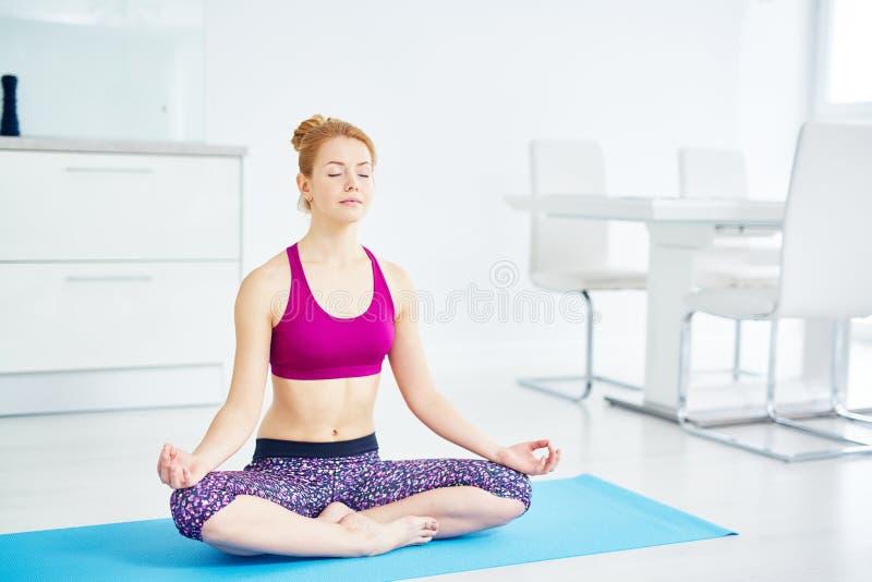 Junge Frau, die zu Hause meditiert stockbild